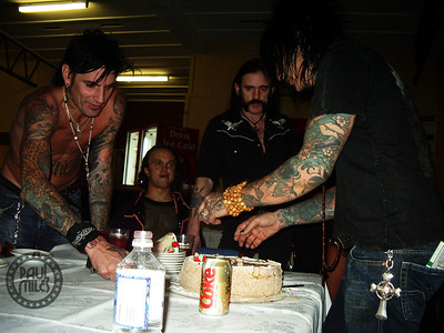Nikki Sixx sharing out his birthday cake to Tommy Lee, Mighty Mike and Lemmy, backstage after the Blackjack Festival on 10 December 2005 at the close of their Australian Tour.