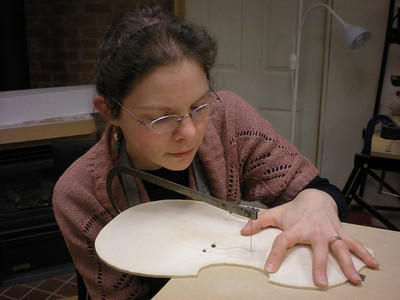 Then the flames are roughly cut using a wide mouthed fret saw with a jeweler's blade. Here Olivia Pelling is working on it.