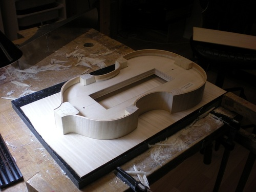 In this case, the back is flattened (somewhat like a guitar back) and very precisely thicknessed.