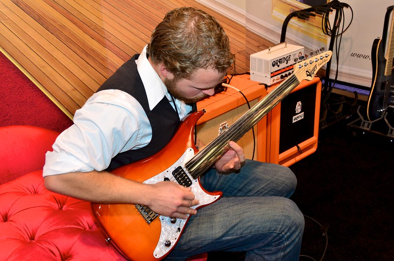 San Diego musician Ryan Woolsley trying out an Orange amplifier with a fretless guitar.