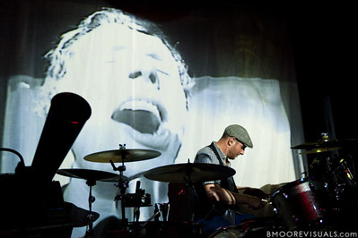 Dan Konopa of OK Go performs while Damian Kulash is projected on the background on May 14, 2010 at Crowbar in Ybor City, Tampa, Florida