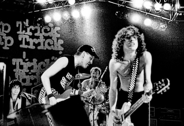 Tom Petersson, Rick Nielsen and Bun E Carlos of Cheap Trick are joined by ACDC's Angus Young on stage.  1979.