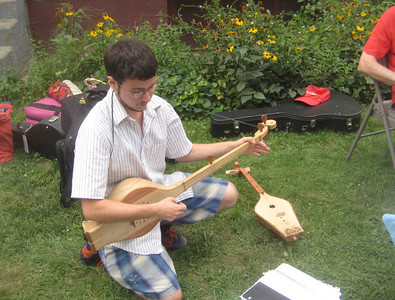 Lysander playing a chonguri from Georgia.  On the ground is his panduri.      See  http://www.atlasofpluckedinstruments.com/middle_east.htm#georgia  (with links to YouTube solos on these instruments)