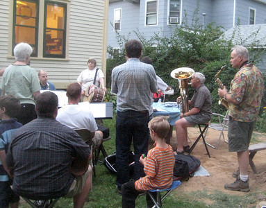 Neighbors (in foreground) listen to the Balkan brass music and add some percussion.