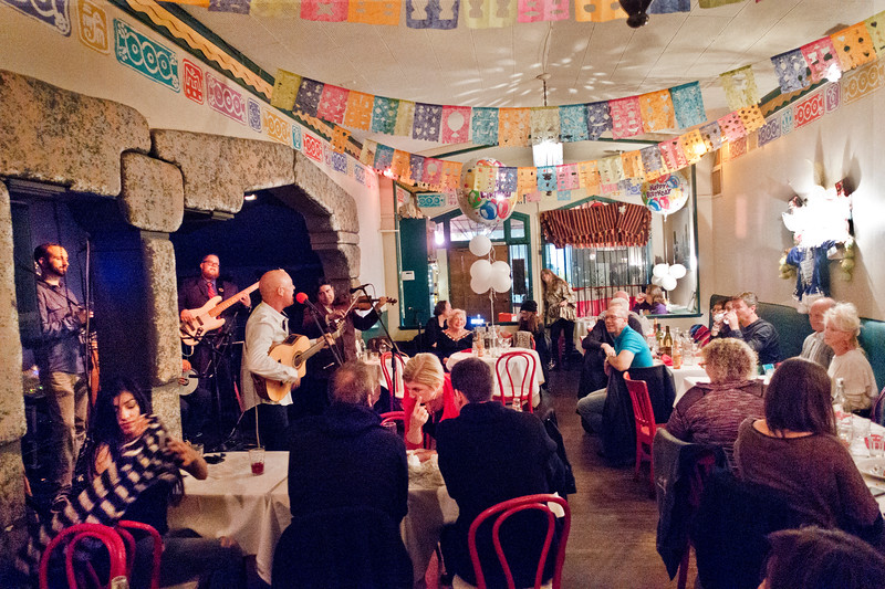 View of restauramt with Freddy Clarke speaking and Pearl Clarke, mother, seated im center - BIRTHDAY PARTY at Peña Pachamama to celebrate Pearl Clarke's birthday. With Wobbly World band and others