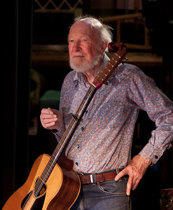 Pete Seeger with his 12 string guitar in the wings before his sound check.