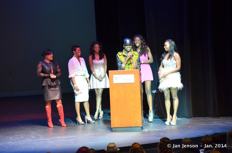 The gals from Prime 1 Realty plus Cordae Gomes  (at podium in green jacket)
