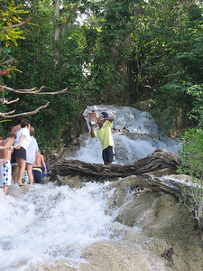 A guide takes video of the tourists as they climbed the falls.