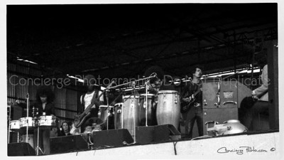 Carlos Santana at the Bath Festival 6-28-1970 - Late Afternoon Set. Carlos Augusto Alves Santana (born July 20, 1947) is a Mexican and American rock guitarist. He became famous in the late 1960s and early 1970s with his band, Santana, which pioneered rock, Latin music and jazz fusion. The band's sound featured his melodic, blues-based guitar lines set against Latin and African rhythms featuring percussion instruments such as timbales and congas not generally heard in rock music. Santana continued to work in these forms over the following decades. He experienced a resurgence of popularity and critical acclaim in the late 1990s. In 2003, Rolling Stone magazine listed Santana at number 15 on their list of the 100 Greatest Guitarists of All Time