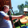 Dan Roberts sprays a finish on a mandolin at the Rocky Grass Academy at Planet Bluegrass Ranch in Lyons on Thursday, July 22.<br /> Greg Lindstrom / The Camera