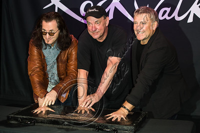 HOLLYWOOD, CA - NOVEMBER 20:  (L-R) Musicians Geddy Lee, Neil Peart and Alex Lifeson of Rush are inducted into Guitar Center's historic RockWalk at Guitar Center on November 20, 2012 in Hollywood, California.  (Photo by Chelsea Lauren/WireImage)