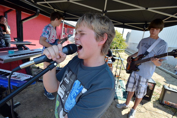 Ethan Oliver, 11, sings vocals with a student band at the opening of the Broomfield School of Rock on Friday.<br /> August 10, 2012<br /> staff photo/ David R. Jennings
