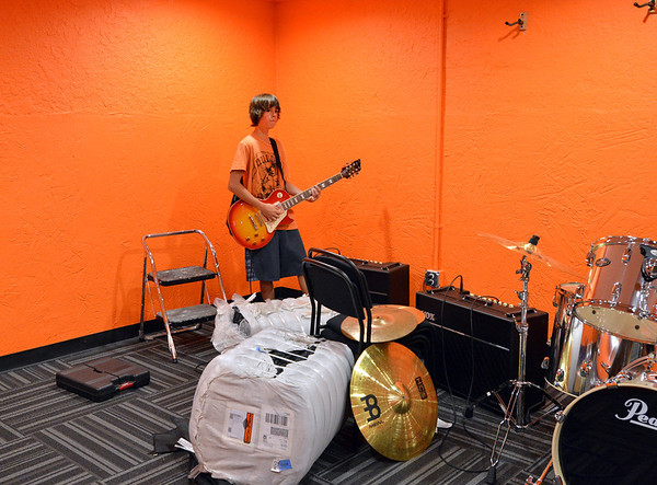 ryan Steinbrecher, 13, plays a guitar in a studio at the opening of the Broomfield School of Rock on Friday.<br /> August 10, 2012<br /> staff photo/ David R. Jennings