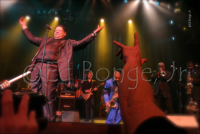 Daryl Brown, front man for the Soul Generals, raises his hands in a spiritual moment, as the band energizes the audience to a James Brown tribute at the NAMM Show, Anaheim, CA.
