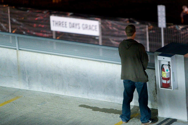A spectator watches and listens to the music from the parkade.