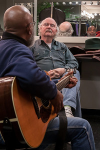 Tom Paxton listening to Josh White Jr. trying out a new song in the green room at Symphony Space, NYC.  That's John Sebastian's hat on the shelf.