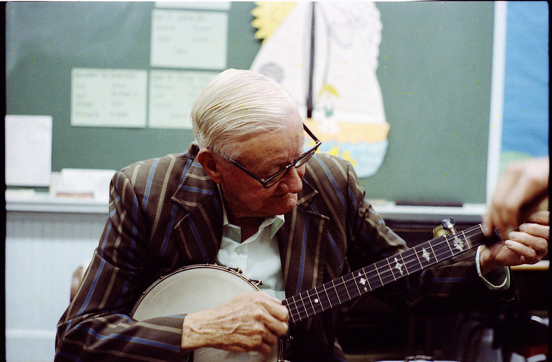 Tommy Jarrell, playing Paul Brown's banjo in a classroom <br /> during the Beulah School fiddle contest, early September 1980.<br /> Tommy did not compete in the contests, but liked to see his old <br /> and new friends who often went to these little gatherings.