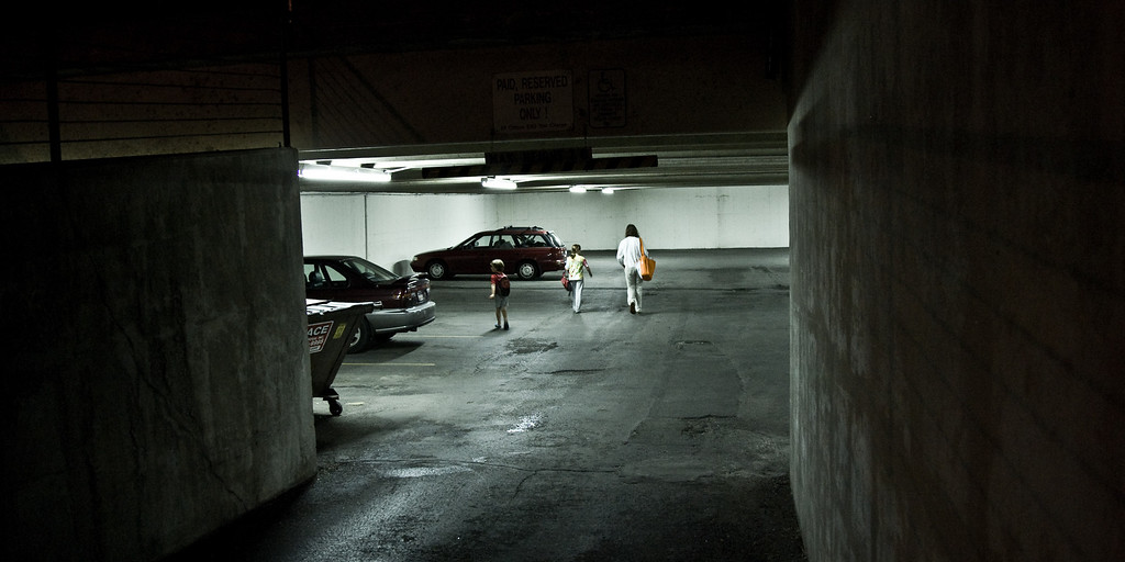 Utah Arts Festival 2008<br /> Returning to our car parked in a nearby underground space. The combination of the dark, hulking concrete at the entrance and the garishly lit cars created a surreal contrast, and I have tweaked the colors to enhance that effect.<br /> aspect ratio 1:2