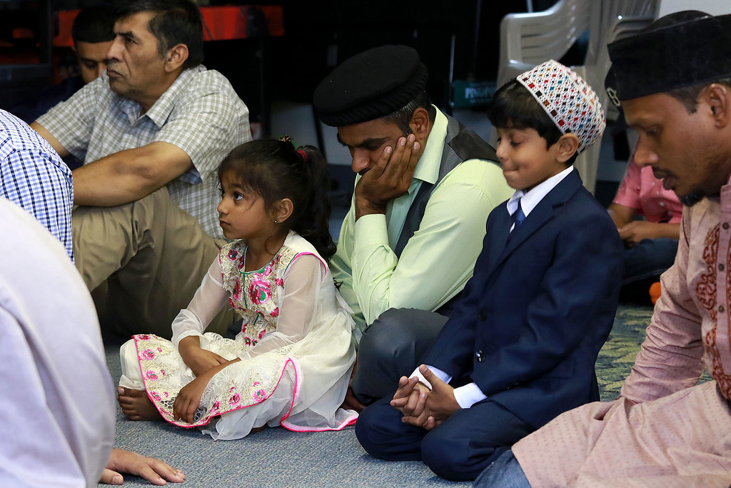""". The Muslim holiday of Eid Al-Adha, also called the \""""Festival of Sacrifice\"""", was celebrated at Masjid Bait-ul-Zikr mosque in Fitchburg on Wednesday morning. Mehtab Saeed, in green shirt, listens to the sermon with his kids Najia Saeed and Khakan Saeed during the ceremony at the mosque. SENTINEL & ENTERPRISE/JOHN LOVE"""