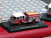 Code 3 1/64 scale Ferrara Hartford Engine 7 sitting on the bumper of the 1/1 scale Engine 7.