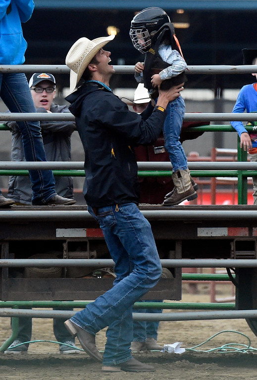. A father, not identified, picks up his child after riding a sheep during the Mutton Busting event on Thursday at the Boulder County Fairgrounds in Longmont. For more photos of the event go to dailycamera.com Jeremy Papasso/ Staff Photographer/ Aug 3, 2017