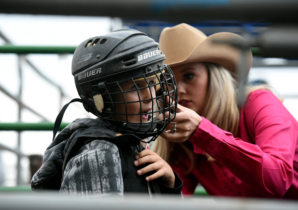 . Cooper Hoen has his helmet adjusted by Mikaela Kugel before riding a sheep during the Mutton Busting event on Thursday at the Boulder County Fairgrounds in Longmont. For more photos of the event go to dailycamera.com Jeremy Papasso/ Staff Photographer/ Aug 3, 2017