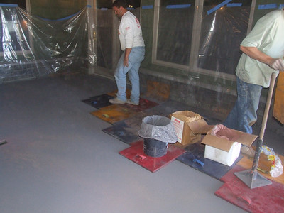 Start of 'stamping' process- they toss different color powders onto the surface of the cement, then use these rubber stamps to shape the surface of the cement