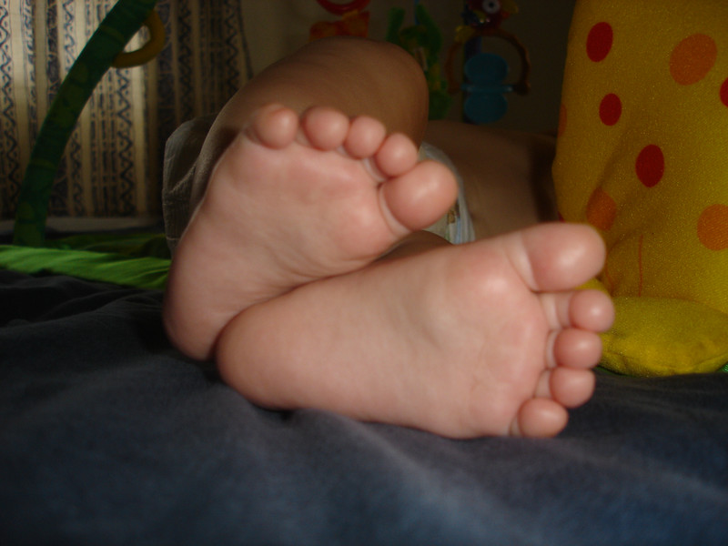 Cayden's baby feet. He is asleep on the bed.