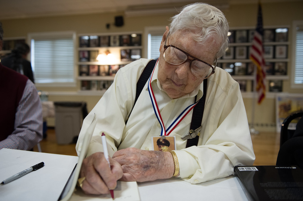 """. 03/26/17 LEOMINSTER with story-- World War II Second Lieutenant Charles R. Rogers signs a book during Sundays book signing of \""""My Father\'s War\"""" written by local author Charley Valera at the Veterans Center in Leominster on March 26, 2017. (Sentinel & Enterprise photo/Jeff Porter)"""