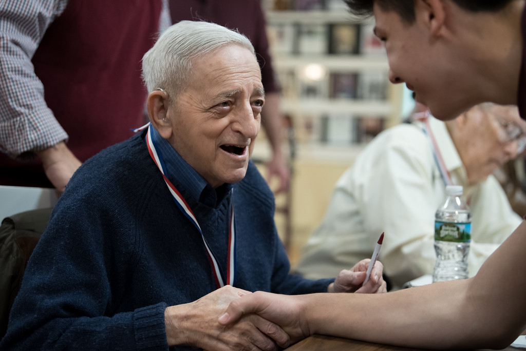 """. 03/26/17 LEOMINSTER with story-- World War II Army Medic Erwin G. Markowitz shakes hands with a young kid during Sundays book signing of \""""My Father\'s War\"""" written by Local author Charley Valera.  The event took place at the Veterans Center in Leominster on March 26, 2017. (Sentinel & Enterprise photo/Jeff Porter)"""