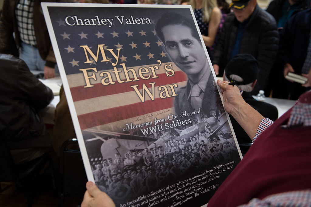 """. 03/26/17 LEOMINSTER with story-- Author Charley Valera holds a large poster featuring the cover of his book \""""My Father\'s War\"""" during Sundays book signing at the Veterans Center in Leominster on March 26, 2017. (Sentinel & Enterprise photo/Jeff Porter)"""
