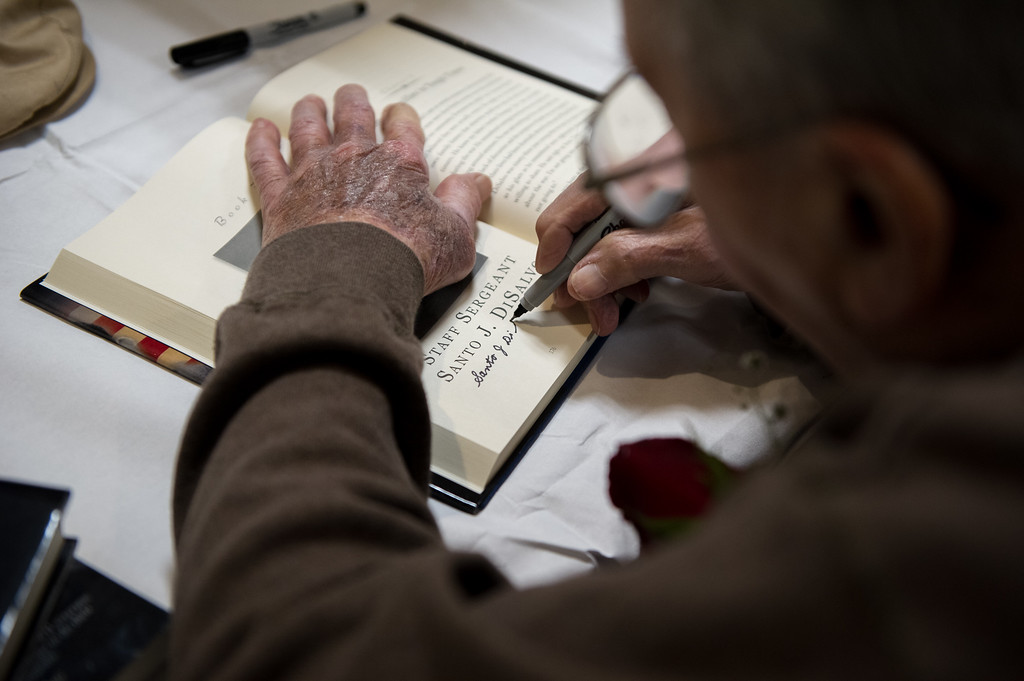 """. 03/26/17 LEOMINSTER with story-- Santo J. DiSalvo signs the page in which he\'s featured in the book \""""My Father\'s War\"""" during Sundays book signing at the Veterans Center in Leominster on March 26, 2017. (Sentinel & Enterprise photo/Jeff Porter)"""