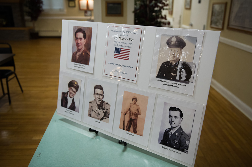 """. 03/26/17 LEOMINSTER with story-- A poster with passed World War II veterans featured in \""""My Father\'s War\"""" sits at the entrance of Sundays book signing at the Veterans Center in Leominster on March 26, 2017. (Sentinel & Enterprise photo/Jeff Porter)"""