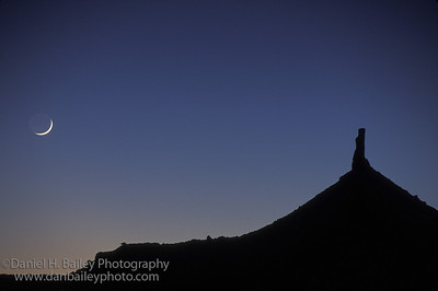 Crescent moon and North Six Shooter tower. Canyonlands, Utah