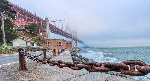 Golden Gate Bridge and Fort Point during gathering morning fog