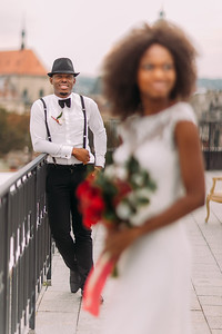 Stylish black groom in focus and his charming bride on the rooftop. Wedding ceremony