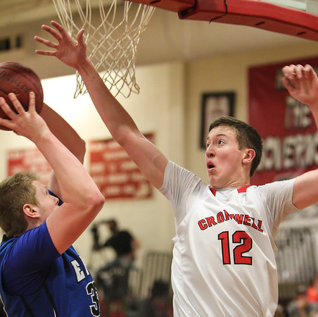Cromwell Panther Matt Turkington blocks a late game jump shot attempt by East Hampton forward Colin Parks during the boys Shoreline League basketball championship game. Cromwell defeated East Hampton 75-56