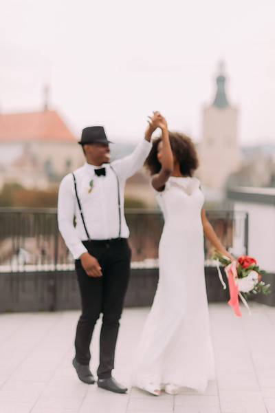 Happy newly wed black couple gracefully dances on the rooftop. Wedding day