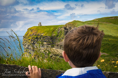 Boy looking at a castle perched on a distant cliff.