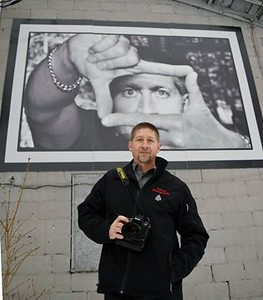 Steve Cain, standing beneath a self-portrait that adorns the side wall of his South March Studio on March Road, has been awarded a national accreditation for general portraiture from the Professional Photographers of Canada, making him one of only 253 professional photographers in Canada to receive the distinction.