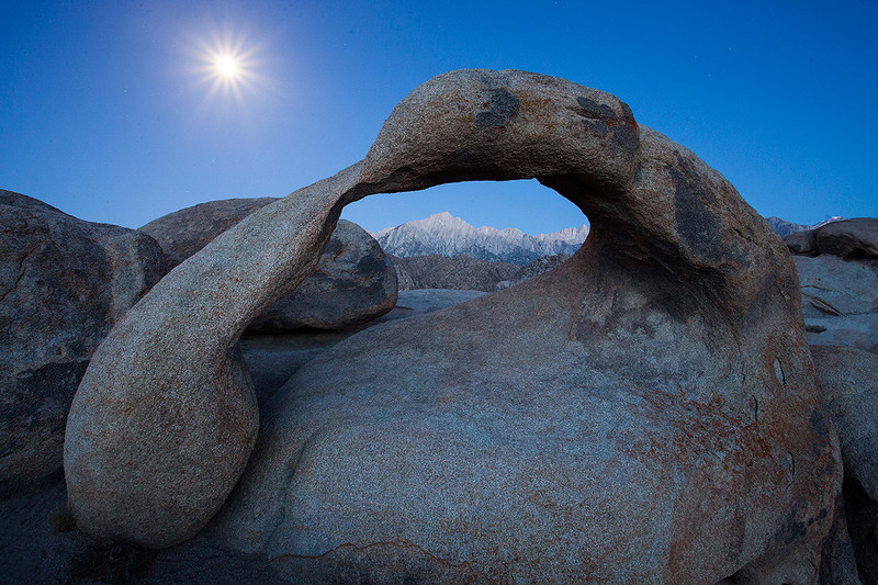 """Mobius Arch""<br /> <br /> Moon setting as the sun begins to rise. Some stars are still visible in the sky."