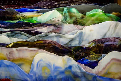 Glass mountains.   Ends cut from sheet glass look like multicolored mountain ranges.