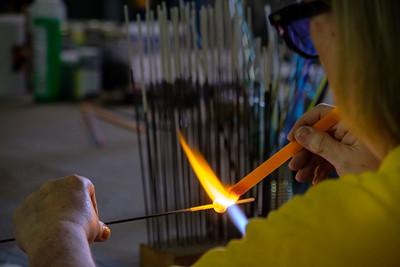 A craftsman working glass into figurines for the gift shop.