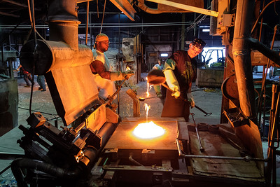 White hot molten glass being deposited on the mixing table.