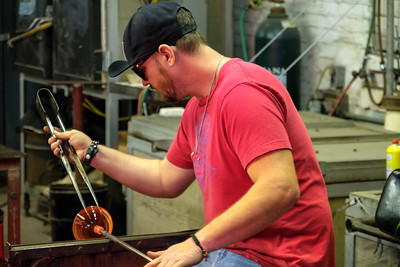 Craftsman creating a glass bowl.