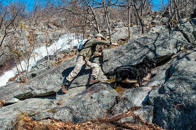 Hiker and dog  scrambling up rocky terrain beside spring melt stream