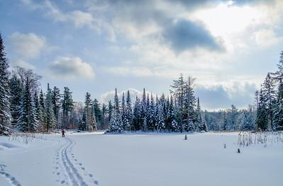 Backcountry glory. Senior male enjoying a peaceful ski through rugged Canadian Shield scenery.