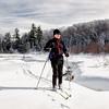 Senior man appreciating the experience while backcountry skiing alongside beautiful creek