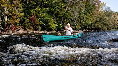 Expert senior paddler and his old  dog run small rapid on the Mississipi River near Carleton Place, Ontario
