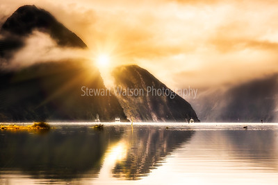 Burst of sunlight through thick cloud and reflections at Milford Sound Fiordland New Zealand